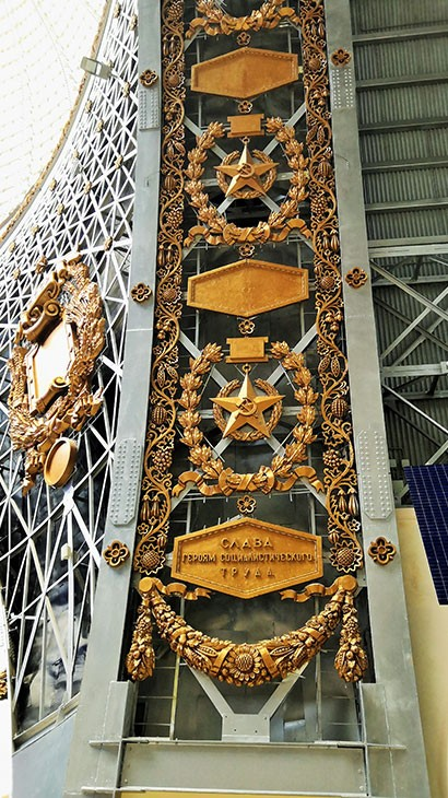 Обезличенные барельефы тружеников космоса сияли вставками декора